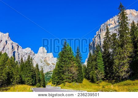 Majestic white mountains and rocks. Serpentine road in the Dolomite Alps. The beautiful sunny day. The concept of active and automobile tourism