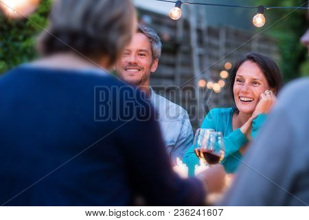 One Summer Evening, Friends Gathered Around A Table In The Garden Lit By Light Garlands. Focus On Be