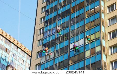 Four Climbers Wash Windows And Glass Facade Of The Skyscraper