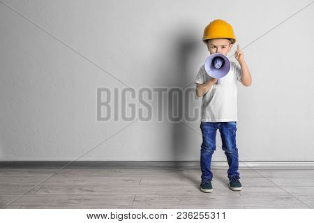 Adorable Little Boy In Hardhat With Megaphone Near Light Wall