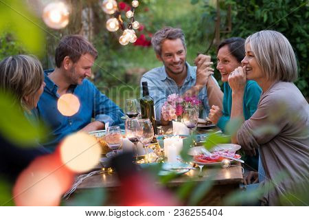 Beautiful Summer Evening In The Garden, A Group Of Friends In Their Forties Have A Good Time Laughin