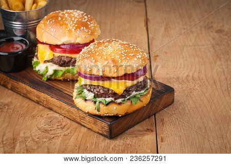 Close-up Of Delicious Fresh Home Made Burger With Lettuce, Cheese, Onion And Tomato On A Rustic Wood