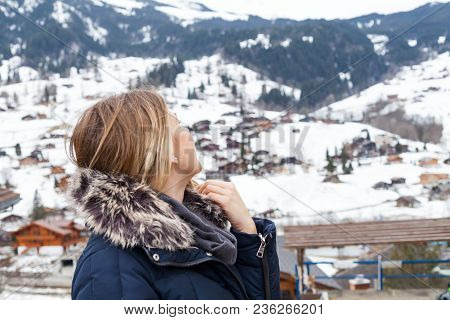 Young Female Tourist Looking To The Snowy Mountains In Grindelwald, Swiss Alps