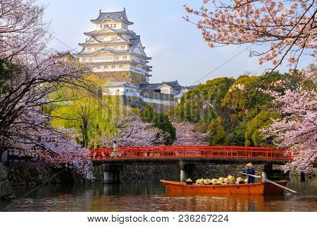 The Himeji castle at full cherry blossom, with tourist boat on the river, Unesco world heritage, Japan