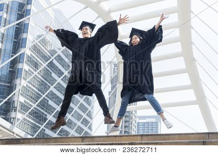 Happy Graduate Teen People Jumping With The Graduation Gowns In Congratulation Ceremony.
