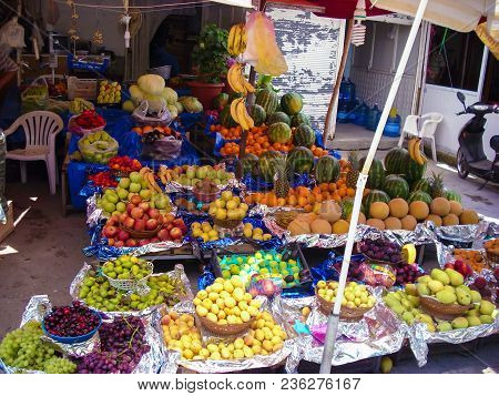Street Fruit Shop In Turkey With Lots Of Fruit For Sale Including Melons, Grapes, Plums, Pears, Appl