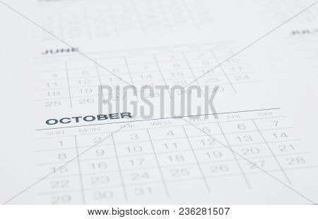 Closeup Calendar Page Focus On October, Blurred The Months Pass, Weekly Start On Sunday. Clean Blue
