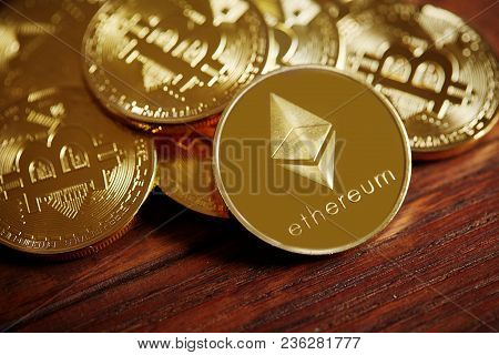 Pile Of Cryptocurrencies Placed On The Wooden Table. Ethereum As Most Important Cryptocurrency Conce