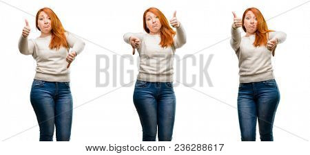 Young Beautiful redhead woman confused with thumbs up and down, trying to take a decision expressing doubt and frustration