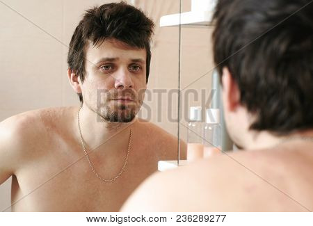 Tired Man Who Has Just Woken Up Looks At His Reflection In The Mirror