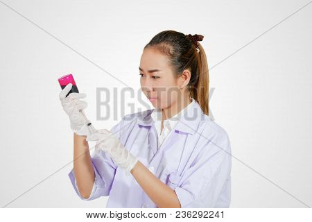 Medical Gloved Hand Holding Syringe With Red Blood Liquid And A Bead Of Liquid Emerging Testing The
