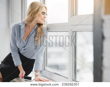 Cheerful Young Businesswoman Is Looking Over The Window With Interest And Smiling. She Is Relaxing O