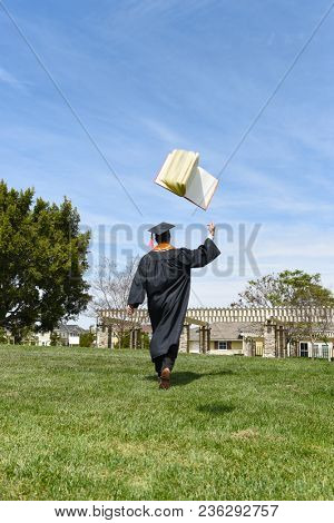 A male graduate in cap and gown with back to the camera tosses a text book in the air. Full lenght as he walsk across grassy field.