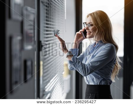 Cheerful Blond Woman Is Looking Over The Window Through Jalousie And Laughing. She Is Standing And S