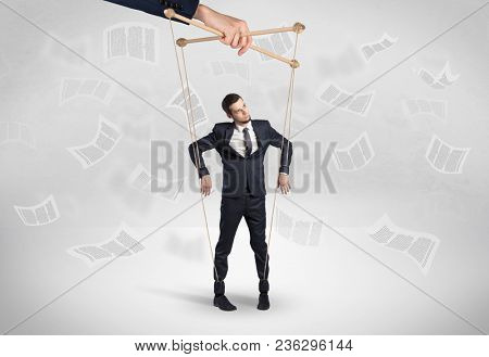 Puppet employee controlled by a big hand with documents and staffs around