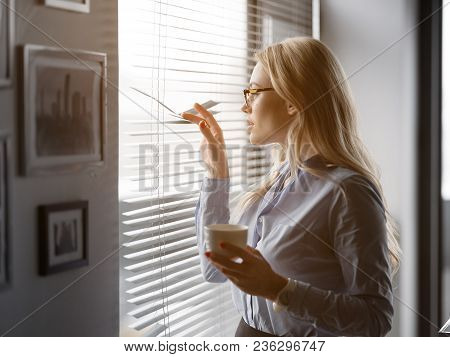 Side View Of Relaxed Young Woman Having Coffee Break In Office. She Is Standing Near Window And Look