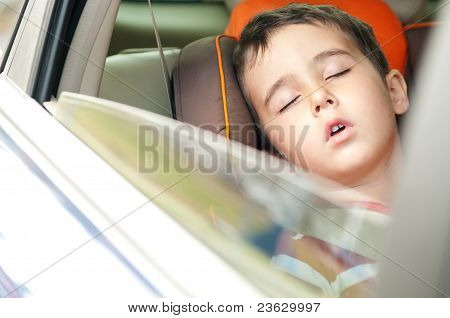 Little boy sleeps in safe chair in car with window open poster