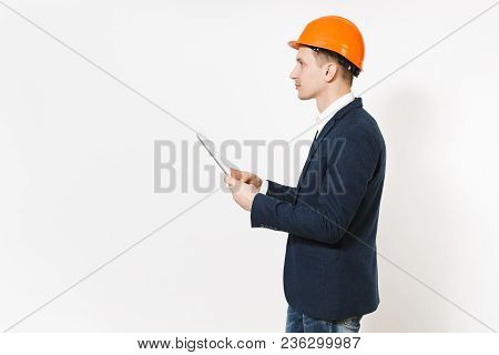 Young Handsome Businessman In Dark Suit, Protective Hardhat Holding Tablet Pc Computer And Looking A