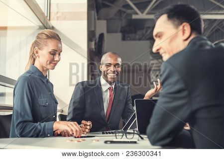 Happy Female And Male Colleagues Speaking With Each Other While Sitting At Table In Office. Beaming
