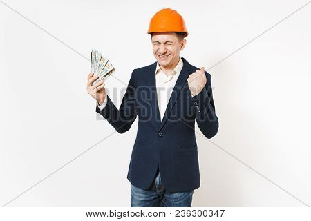 Overjoyed Businessman In Dark Suit, Protective Hardhat Holding Bundle Of Dollars, Cash Money And Doi