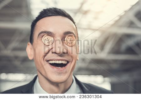 Portrait Of Satisfied Male Worker Holding Bitcoins On Eyes. He Looking At Camera. Glad Rich Employer