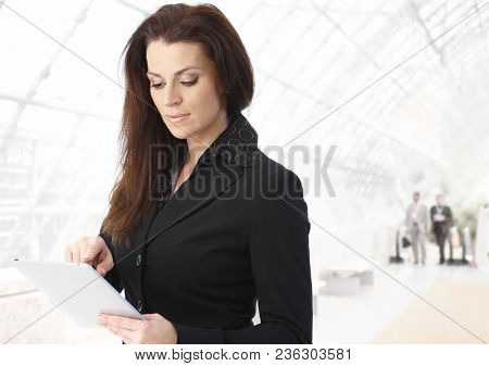 Businesswoman using tablet computer in office building, looking down, smiling.