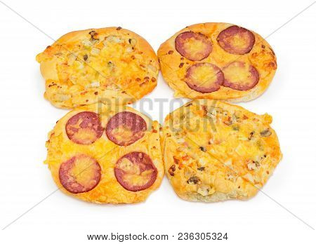 Four Different Small Cooked Round Pizza With Sausage And Chicken On A White Background