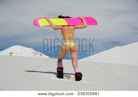Back View Of Young Sexy Girl Dressed In A Bright Yellow Swimsuit With A Snowboard On The Shoulders