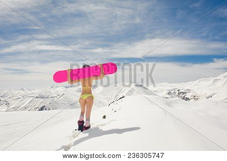 Back View Of Sexy Girl Dressed In A Bright Yellow Swimsuit With A Snowboard On The Shoulders Walking