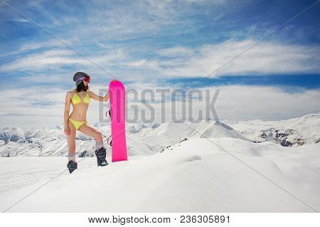 Attractive Sexy Woman In Swimsuit And Helmet With A Snowboard On The Background Of High Mountains