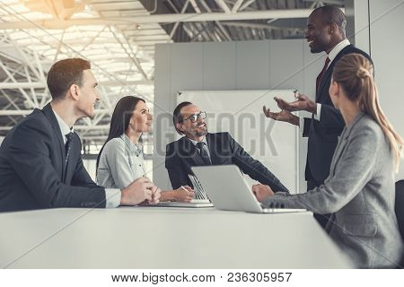 Outgoing Colleague Describing Presentation For Satisfied Partners While Standing Opposite Them. They