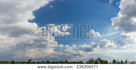 Background Of A Panoramic View Of The Sky With Cumulus Clouds And Sunbeams From Behind A Cloud In Sp