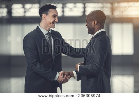 Side View Outgoing Worker Telling With Partner While Greeting With Him. Glad Colleagues During Commu