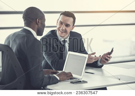 Portrait Of Cheerful Male Telling With Colleague While Holding Phone In Arm. Employer Typing In Lapt