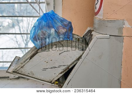 Garbage bag full of a garbage lying in a lid of a home garbage chute in Moscow dwelling house poster