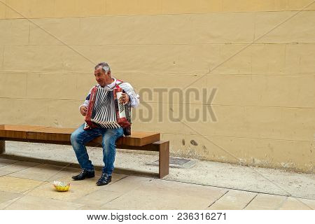 Malaga, Spain - April 10, 2018. Unidentified Street Musician Playing Melodies With His Old Accordion