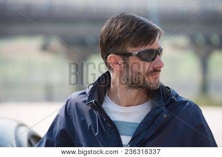 Portrait Of A Bearded Man In Sunglasses Looks Around. Age Of Forty Years.