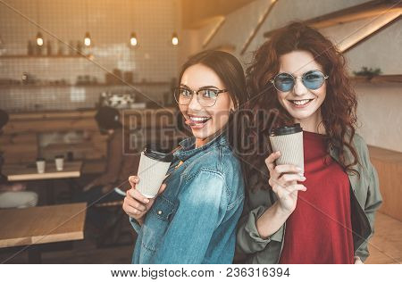 Waist Up Portrait Of Two Outgoing Girls Standing And Posing In Cafeteria. They Are Holding Cups Of E