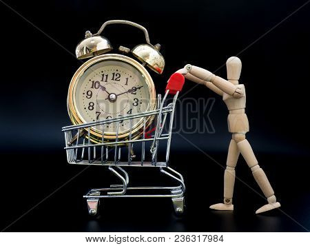 Puppets Are Holding A Shopping Cart. There Is A Golden Vintage Clock Inside On Black Background. The