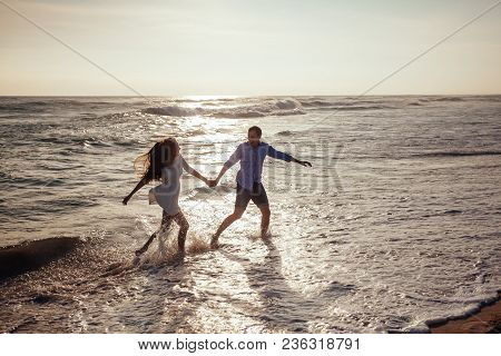Happy Cheerful Couple Having Fun Running To The Ocean Together And Doing Splashes Of Water On A Trop