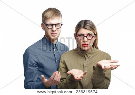 Two Employees Wearing Eyeglasses Having Displeased Expressions, Grimacing And Gesturing In Confusion