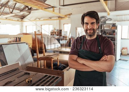 Portrait Of A Smiling Young Craftsman Standing With His Arms Crossed By A Bench Saw In His Workshop