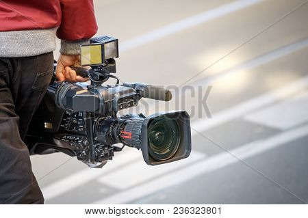 Cameraman Holding His Professional Camcorder In The Street. Operator In Social Environment, Filming,