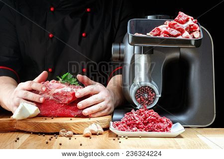 Professiona Chef Prepares Minced Meat From Fresh Meat On Dark Background.  Horizontal View.