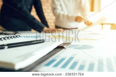 Two Businessmen In A Meeting And Standing At Boardroom Table Having Discussion.