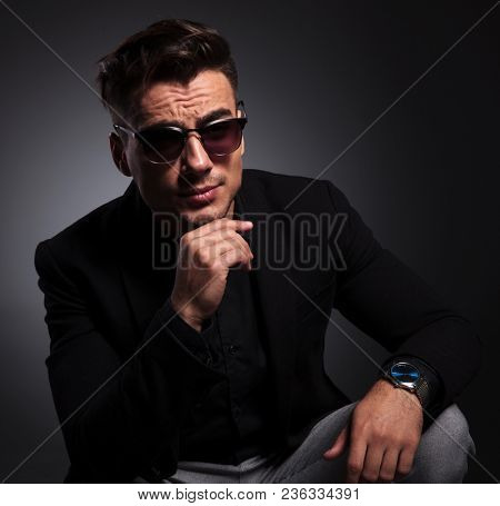 portrait of young fashion man with sunglasses sitting and thinking on black and gray background while looking to side