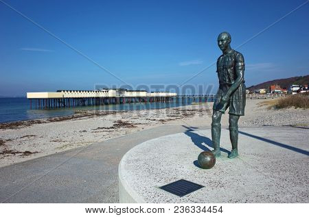 Helsingborg, Sweden - 14 April, 2018: Sculpture of Henrik Larsson, He played with Helsingborg, Celtic, Barcelona and Man United football teams in his career, Famous Palsjobaden bathhouse in distance
