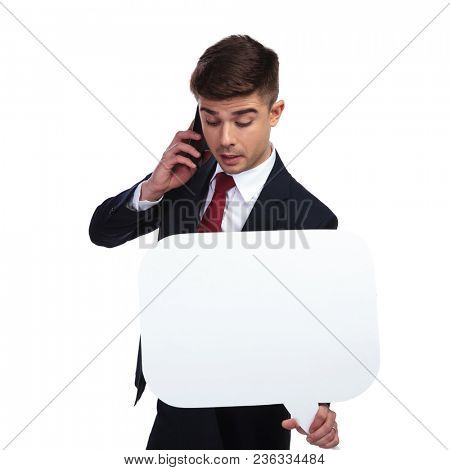 businessman with speech bubble having an important telephone call while standing on white background. In this portrait he wears a navy suit and a red tie and looks extremely busy.