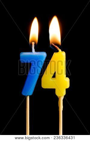 Burning Candles In The Form Of 74 Seventy Four (numbers, Dates) For Cake Isolated On Black Backgroun
