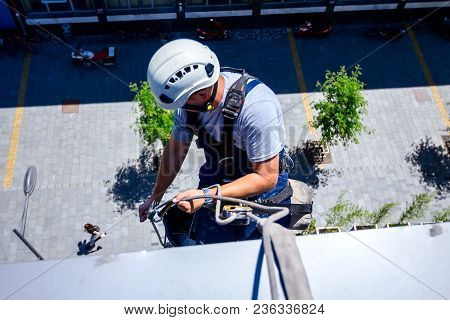 Industrial Climber, Alpinist, Is Adjusting Climbing Gear, Preparing Safety Ropes.